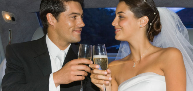 Groom and bride drinking champagne in a limo